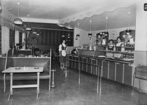 Tre bunadskledde ansatte på Fønix kafe i et tidstypisk kafeinteriør, fotografert i 1960. Hva damene heter er ikke registrert på Mjøsmuseets arkivkort. (Foto: Mjøsmuseet).