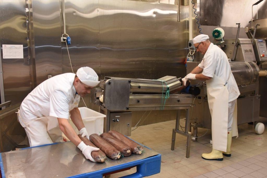 Toten Kjøtt produserer 1200 tonn i året. Halvparten av volumet er medisterfarse. Men bedriften lager en rekke produkter. Her er Slawomir Neuman (til venstre) og Besim Rushitic i ferd med å kjøre ut spekepølse.